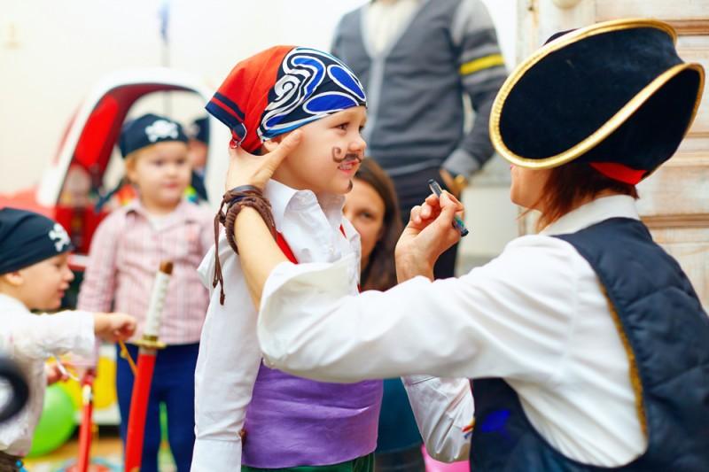 Kinder werden am Kindergeburtstag zu Piraten geschminkt.