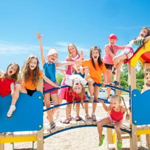 Fröhliche Kinder spielen auf einem Spielplatz am Kindergeburtstag.
