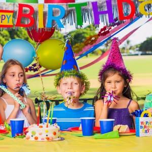 Froehliche Kinder vor dem Geburtstagstisch