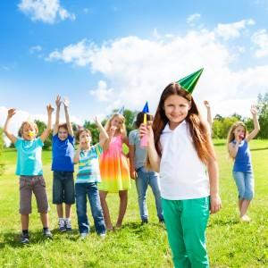 Kinder freuen sich auf einer Wiese beim Kindergeburtstag