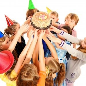 Kinder halten Geburtstagstorte beim Kindergeburtstag in die Luft