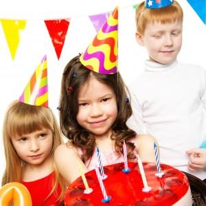 Geburtstagskind präsentiert Ihren Geburtstagskuchen am Kindergeburtstag mit zwei Geburtstagsgästen